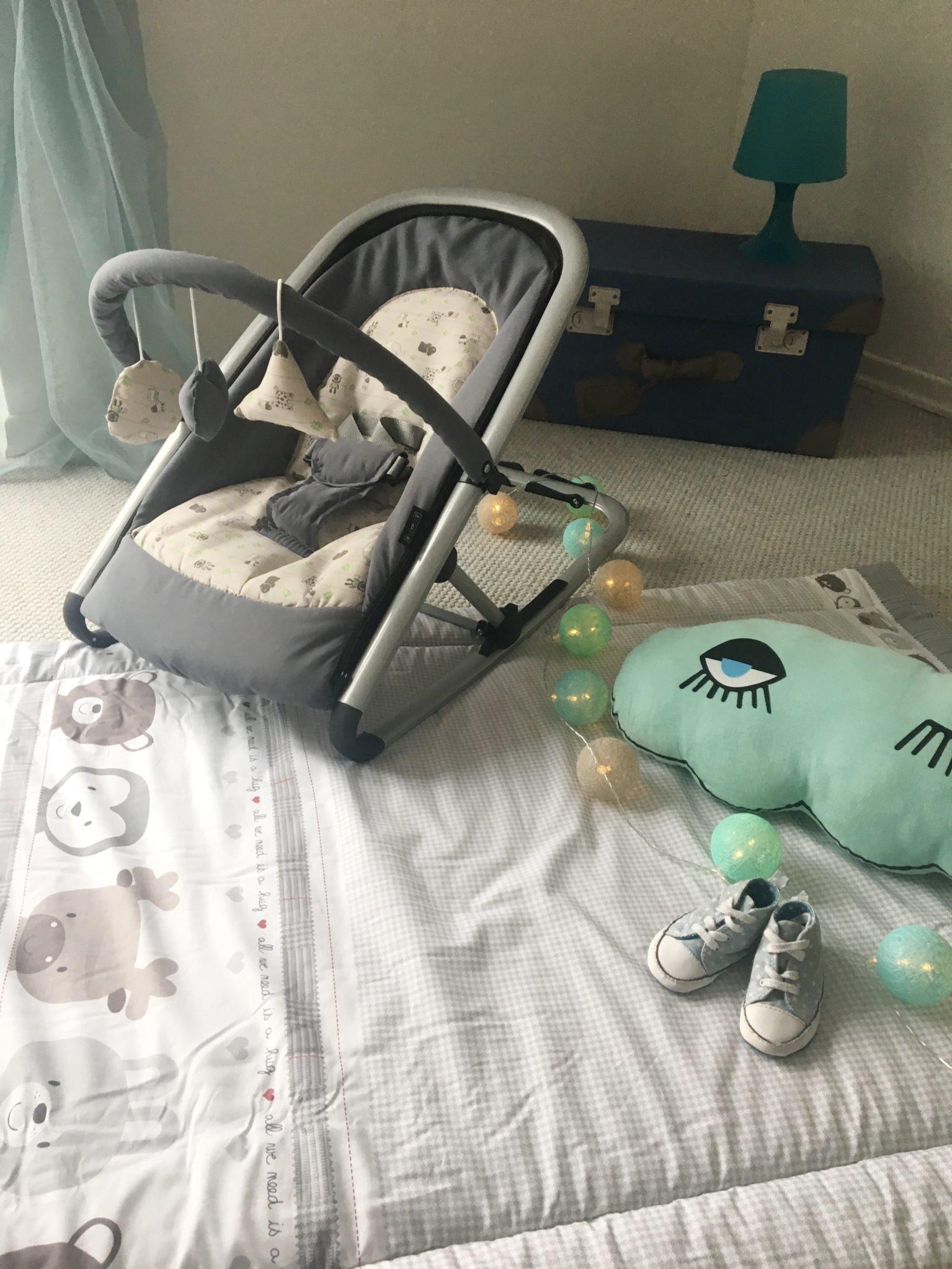 Babyausstattung: Krabbeldecke und Babywippe.